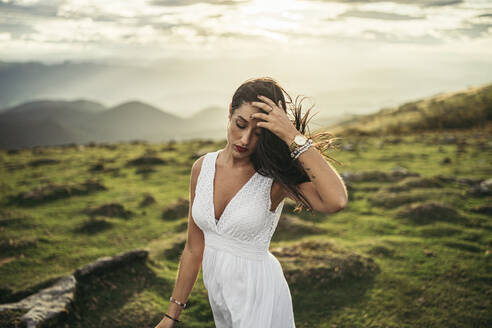 Young woman wearing white dress on viewpoint at sunset - MTBF00161