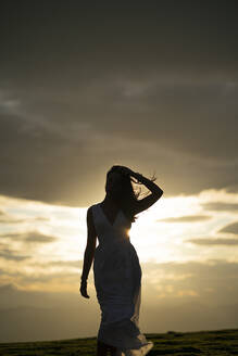 Young woman wearing white dress at sunset - MTBF00167