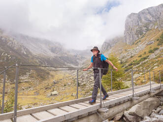 Hiker walking over a footbridge in the mountains, nature park Adamello, Italy - LAF02410