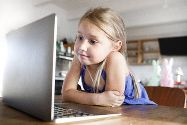 Portrait of little girl leaning on kitchen table at home looking at laptop - KMKF01133