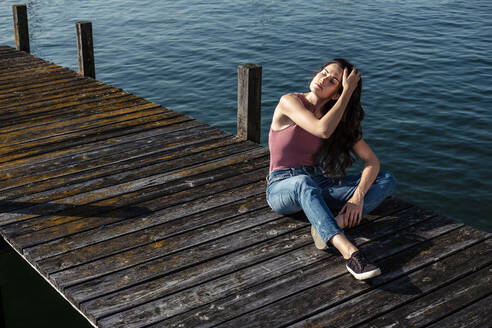 Young woman with eyes closed realxing on jetty, Lake Starnberg, Germany - WFF00153