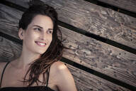 Portrait of smiling young woman relaxing on jetty - WFF00162
