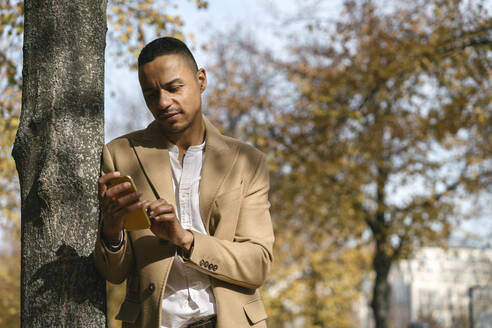 Portrait of businessman leaning against tree trunk in autumn looking at cell phone - AHSF01075