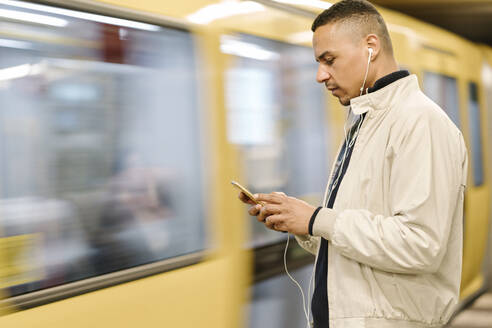 Man standing at underground station platform using earphones and cell phone, Berlin, Germany - AHSF01090