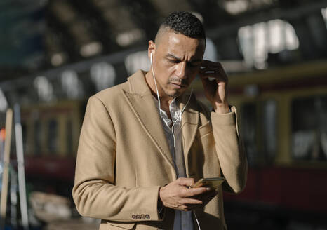 Businessman at train station Alexanderplatz using earbuds and smartphone, Berlin, Germany - AHSF01099