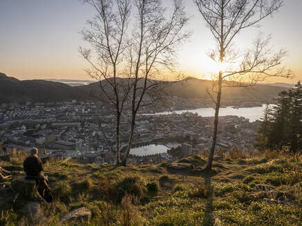 Norway, Bergen, Person admiring sunset from top of hill overlooking coastal city - JMF00455