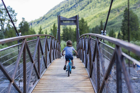 Rear view of 5 year old boy on mountain crossing narrow bridge - MINF12767