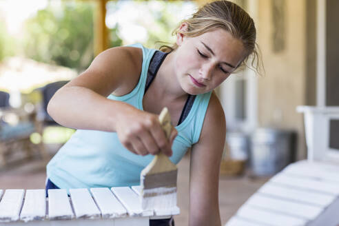 A teenage girl painting furniture white - MINF12788
