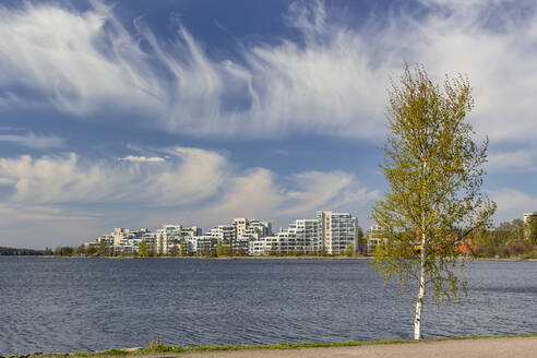 Finland, Lahti, Clouds over Vesijarvi lake and modern residential buildings in spring - MELF00210