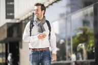 Smiling young man with backpack and cell phone in the city on the go - UUF19574