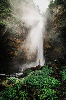 Male tourist in Indonesia looking at waterfall while sitting on rocks - CAVF68583