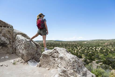 Rear view of teenage girl hiker overlooking desert vista at the Tsankawi Ruins - MINF13238