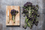 High angle close up of purple sprouting broccoli, knife and wooden cutting board. - MINF13286