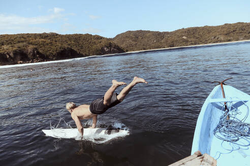 Shirtless man with surfboard jumping into sea against sky during sunny - CAVF68711