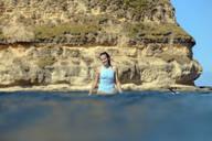 Happy woman sitting on surfboard in sea - CAVF68717