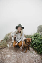 Young woman with two dogs on viewpoint - LHPF01135