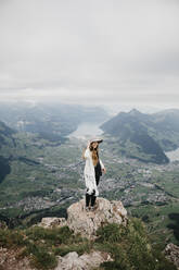 Young woman wearing hat, standing on viewpoint, Grosser Mythen, Switzerland - LHPF01138