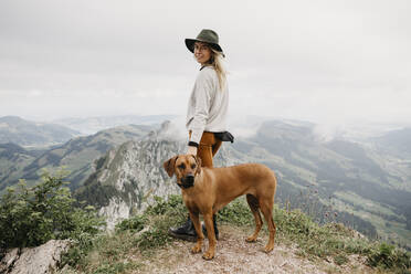 Woman with dog on viewpoint, Grosser Mythen, Switzerland - LHPF01147