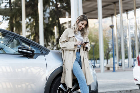 Young blond woman using smartphone, leaning on a car - ERRF02028