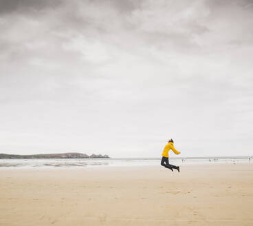 Young woman wearing yellow rain jacket at the beach, Bretagne, France - UUF19651