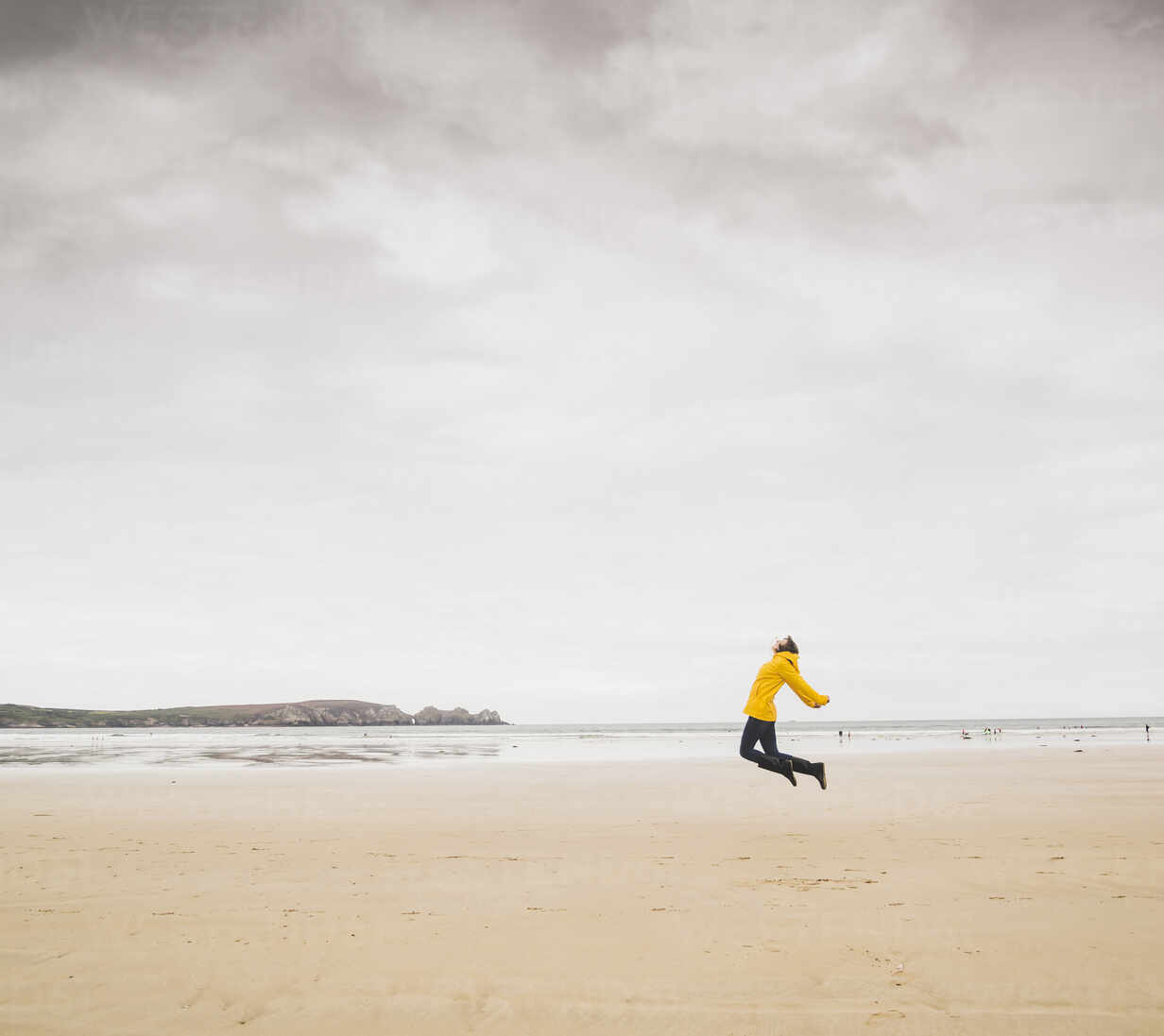 Young woman wearing yellow rain jacket at the beach, Bretagne, France - UUF19651 - Uwe Umstätter/Westend61
