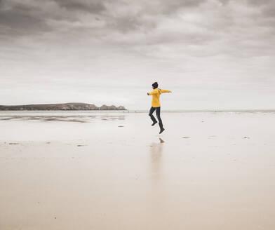 Young woman wearing yellow rain jacket, jumping at the beach, Bretagne, France - UUF19654