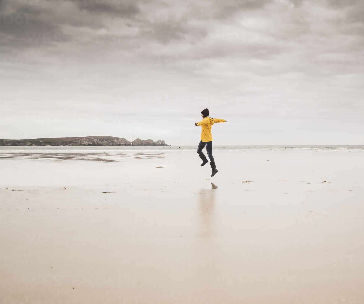 Young woman wearing yellow rain jacket, jumping at the beach, Bretagne, France - UUF19654 - Uwe Umstätter/Westend61