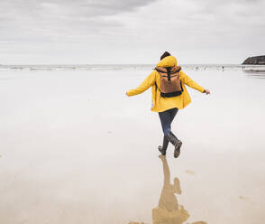 Young woman wearing yellow rain jacket and running at the beach, Bretagne, France - UUF19657