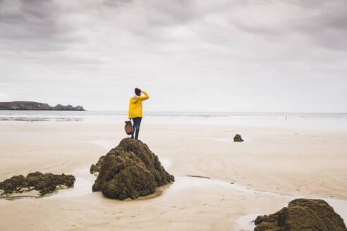 Young woman wearing yellow rain jacket at the beach, Bretagne, France - UUF19660