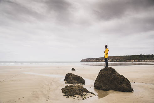 Young woman wearing yellow rain jacket at the beach, Bretagne, France - UUF19663