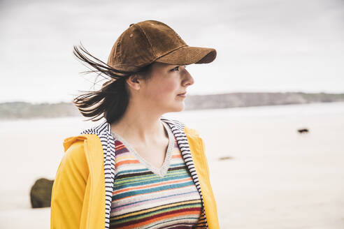 Portrait of young woman wearing yellow rain jacket at the beach, Bretagne, France - UUF19666