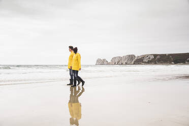 Young woman wearing yellow rain jackets and walking along the beach, Bretagne, France - UUF19672