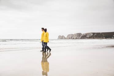Young woman wearing yellow rain jackets and walking along the beach, Bretagne, France - UUF19672