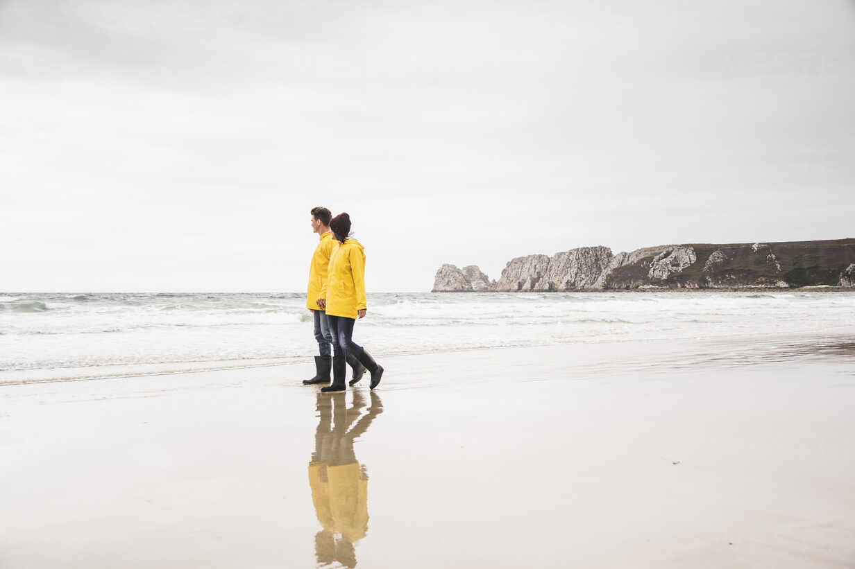 Young woman wearing yellow rain jackets and walking along the beach, Bretagne, France - UUF19672 - Uwe Umstätter/Westend61