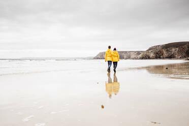Young woman wearing yellow rain jackets and walking along the beach, Bretagne, France - UUF19675
