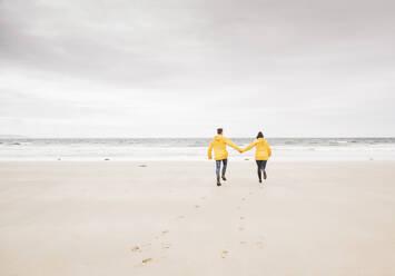 Young woman wearing yellow rain jackets and walking along the beach, Bretagne, France - UUF19678
