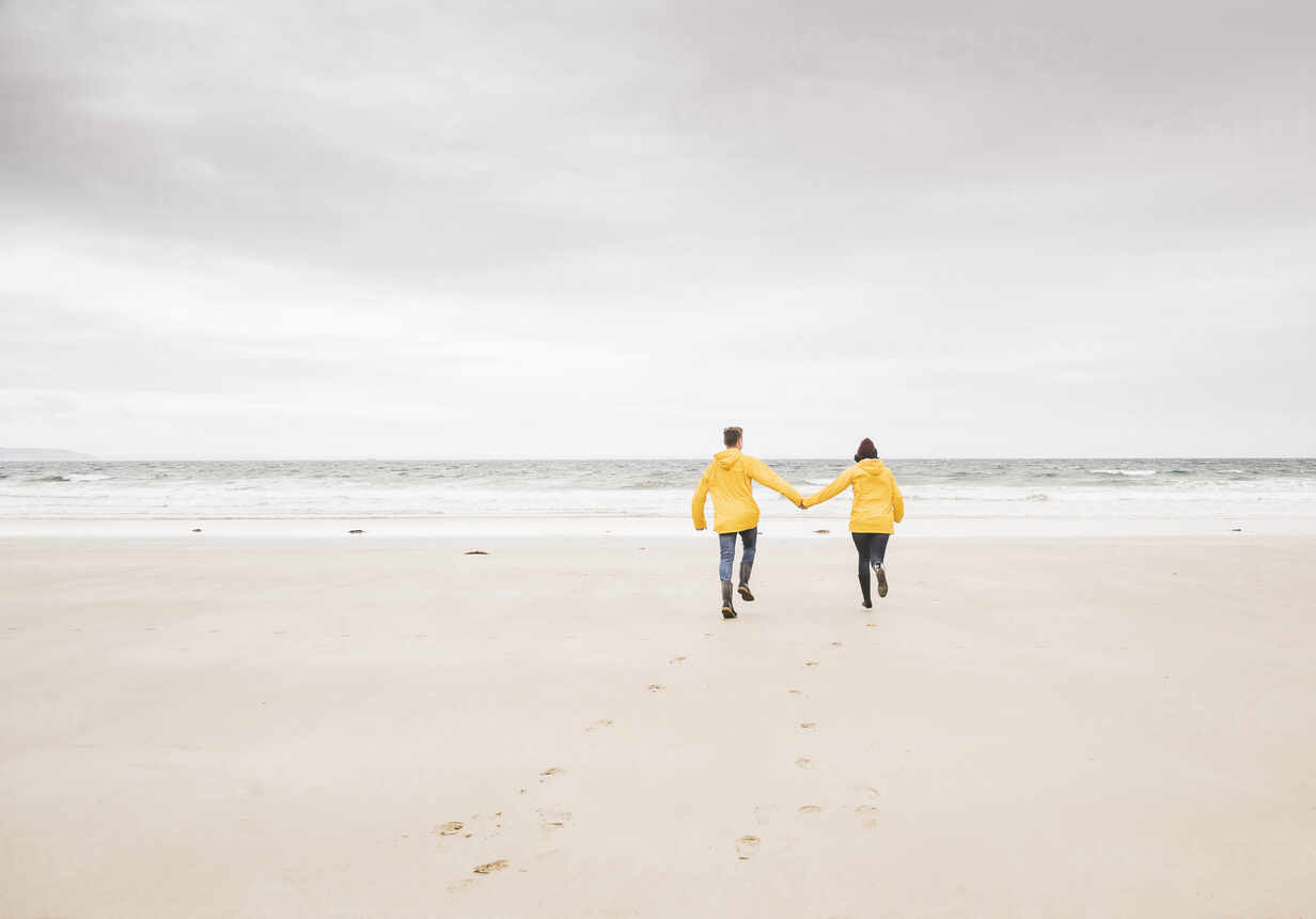 Young woman wearing yellow rain jackets and walking along the beach, Bretagne, France - UUF19678 - Uwe Umstätter/Westend61