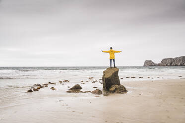 Young man wearing yellow rain jacket at the beach and standing on rock, Bretagne, France - UUF19681