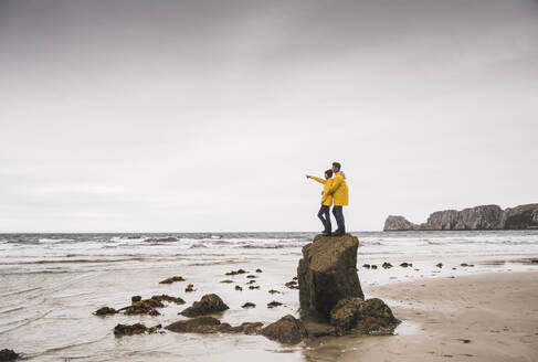 Young woman wearing yellow rain jackets and standing on rock at the beach, Bretagne, France - UUF19684
