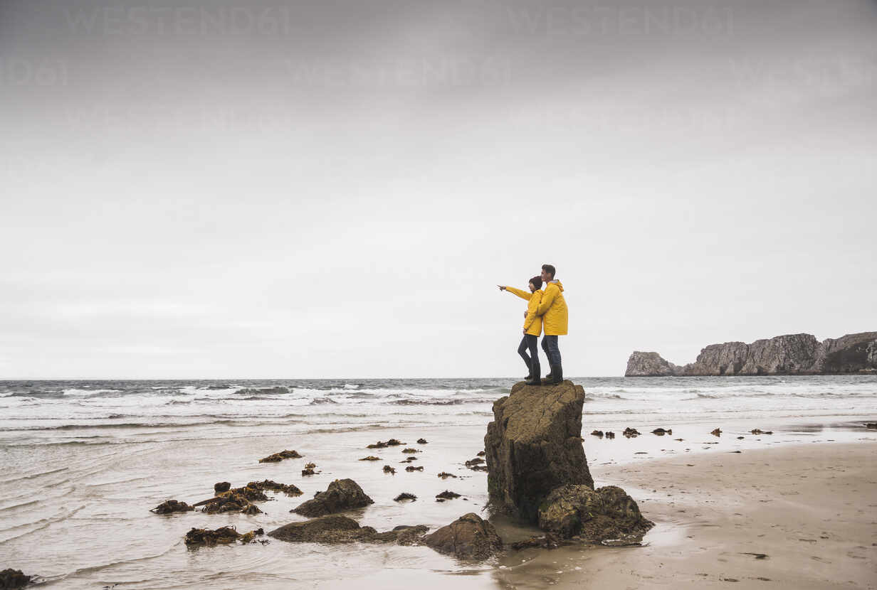 Young woman wearing yellow rain jackets and standing on rock at the beach, Bretagne, France - UUF19684 - Uwe Umstätter/Westend61