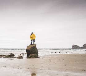 Young woman wearing yellow rain jackets and standing on rock at the beach, Bretagne, France - UUF19687