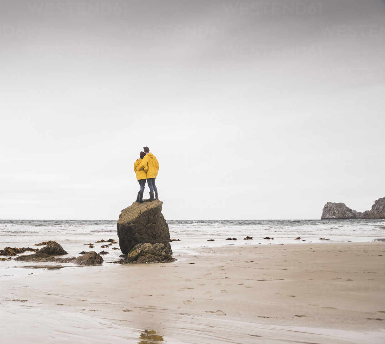 Young woman wearing yellow rain jackets and standing on rock at the beach, Bretagne, France - UUF19687 - Uwe Umstätter/Westend61