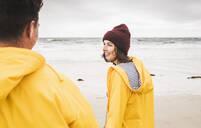 Young woman wearing yellow rain jackets and walking along the beach, Bretagne, France - UUF19690
