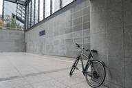 Black bicycle leaning against wall of station building at Potsdamer Platz, Berlin, Germany - AHSF01145