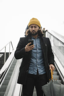 Portrait of man with umbrella standing on escalator looking at smartphone - AHSF01148
