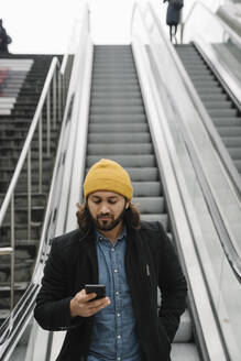 Portrait of bearded man standing on escalator looking at smartphone - AHSF01151