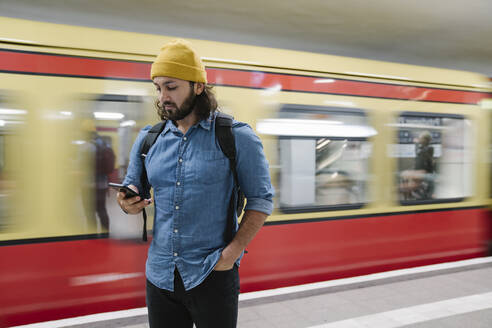 Bearded man with backpack looking  at smartphone while waiting at platform, Berlin, Germany - AHSF01166