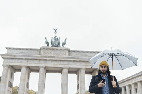 Man with umbrella using smartphone in front of Branderburg Gate, Berlin, Germany - AHSF01175