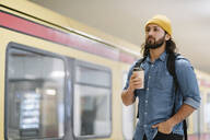 Portrait of man with backpack and coffee to go waiting at platform, Berlin, Germany - AHSF01181