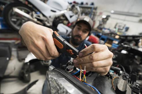 Mechanic in a repair garage repairing a motorcycle - MTBF00174